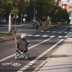 An elderly woman using an electric wheelchair in a bike lane