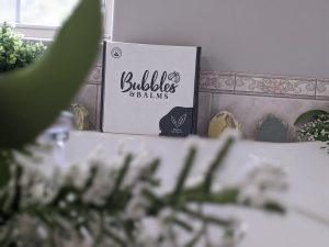 Une boîte Bubbles & Balms se trouve sur un comptoir à côté de pains de savon